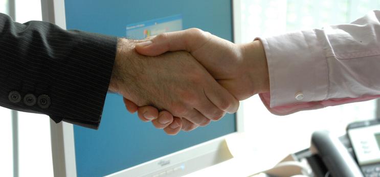 Detailaufnahme eines Händeschüttelns in Büroumgebung